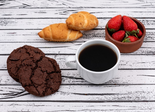 Side view of coffee with cookies and croissants with strawberry on white wooden surface horizontal Free Photo