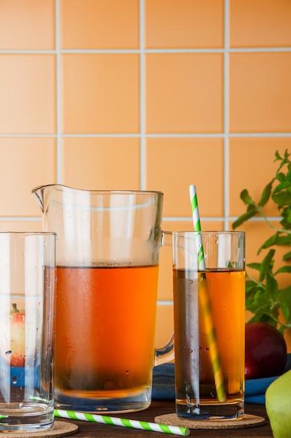 オレンジ色のタイルの背景のテーブルに側面ビュー冷たいリンゴジュース。テキストの垂直方向のスペース 無料写真