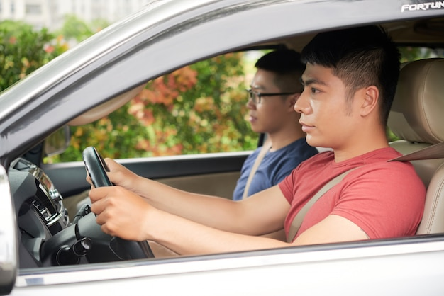 Side view of confident asian man driving car with his friend as passenger Free Photo