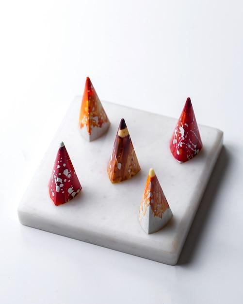 Вид сбоку конический разноцветный в белой крапинке шоколадные конфеты на белой подставке Бесплатные Фотографии