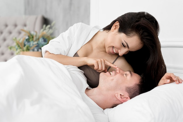 Side view of couple being romantic in bed Free Photo
