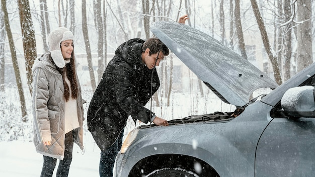Side view of couple checking car engine while on a road trip Free Photo