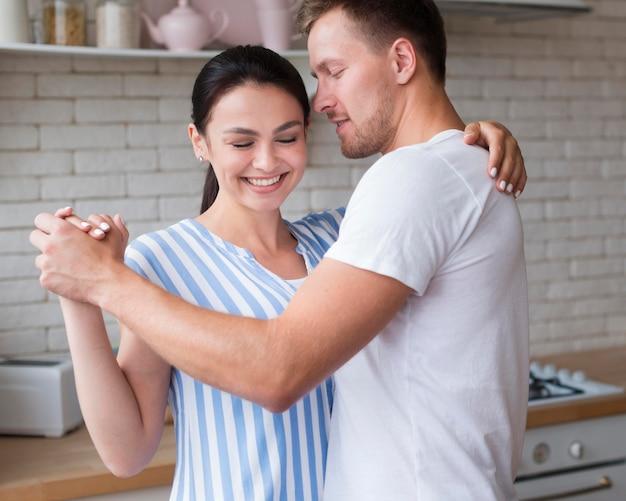 Боковой вид пара танцует в помещении Бесплатные Фотографии