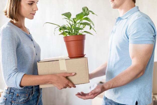Vista laterale della coppia che maneggia scatole e pianta mentre si prepara a muoversi Foto Gratuite