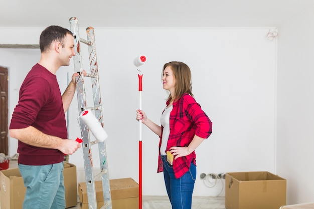 Side view couple with paint rollers and ladder Free Photo