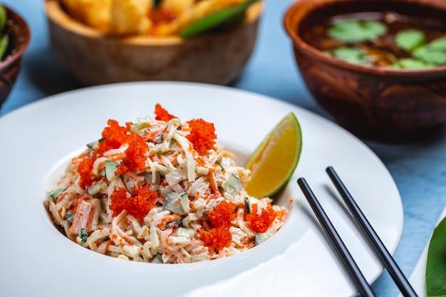 Vista laterale granchio insalata cetriolo riso granchio carne tobiko caviale maionese e fetta di lime su un piatto Foto Gratuite