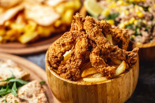 Side view crispy fried chicken tenders with french fries Free Photo