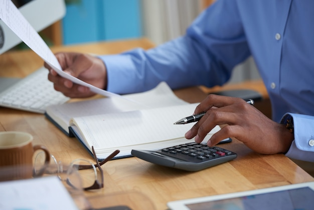 Side view of cropped man working on financial report Free Photo