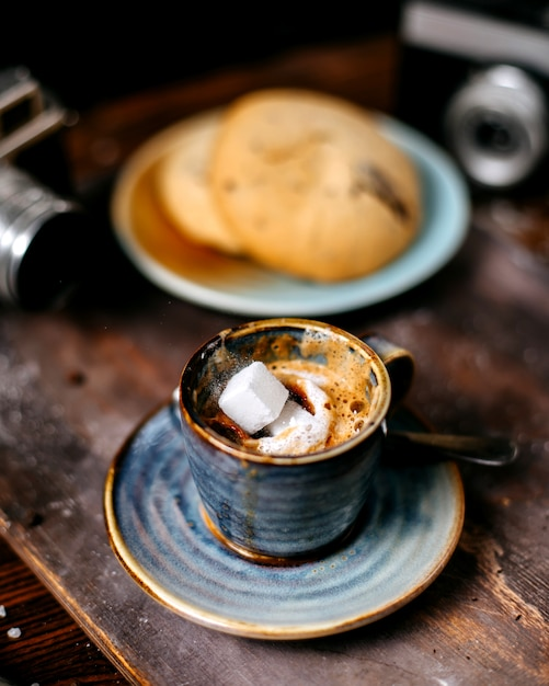 Side view of a cup of coffee espress with cookies on rustic backgraund Free Photo