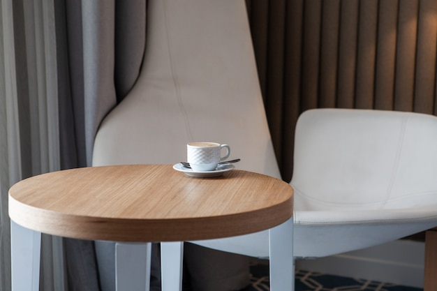 Side view cup of coffee on a small round table horizontal Free Photo