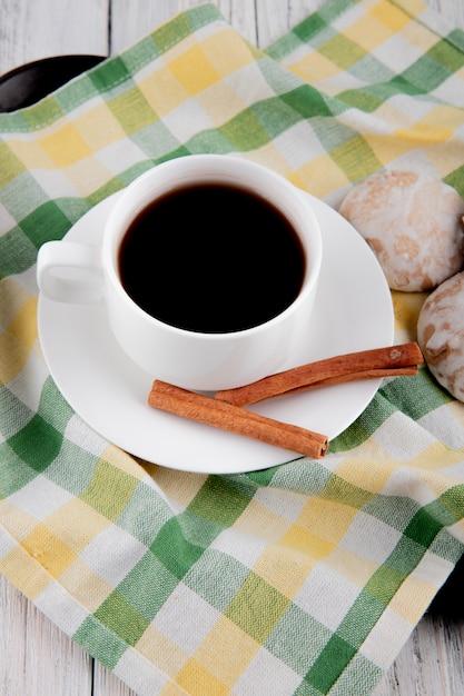Вид сбоку чашка кофе с корицей и пряниками на скатерти Бесплатные Фотографии