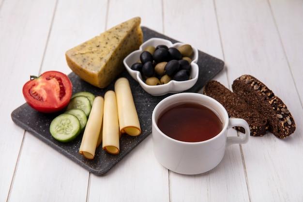 オリーブトマトキュウリと白い背景の上の黒いパンのスライスとスモークチーズとお茶の側面図 無料写真