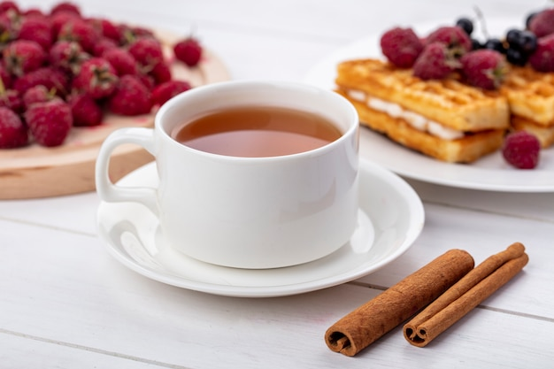 Side view of cup of tea with cinnamon white cherries and sweet waffles with raspberries on a white surface Free Photo