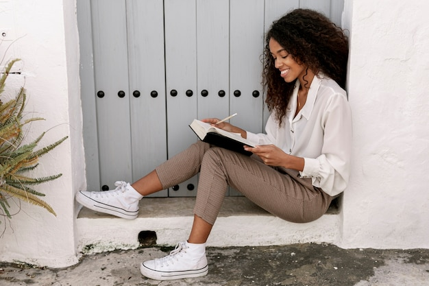 Side view curly woman reading a book Free Photo