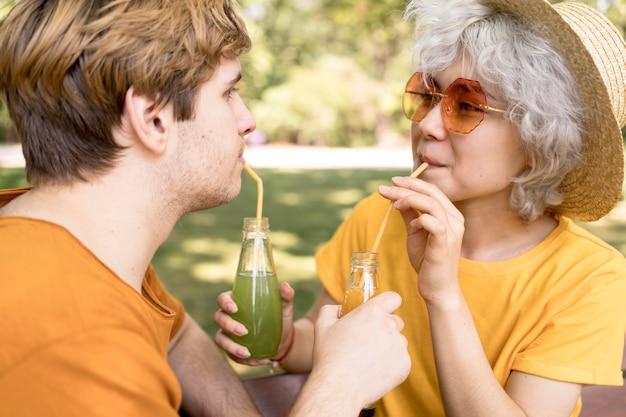 Vista laterale della coppia carina bere succo di frutta nel parco con cannucce Foto Gratuite
