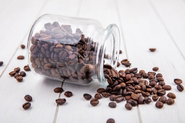 Vista laterale dei chicchi di caffè tostati scuri che cadono da un barattolo di vetro su un fondo di legno bianco Foto Gratuite