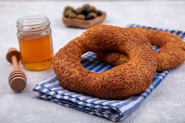Vista laterale di deliziosi e morbidi bagel turchi tradizionali isolati su un panno controllato con miele e miele cucchiaio su uno sfondo bianco Foto Gratuite