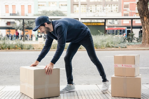 Side view of a delivery man carrying cardboard box Premium Photo