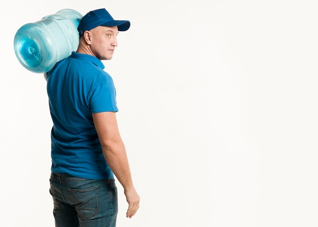 Side view of delivery man carrying water bottle Free Photo