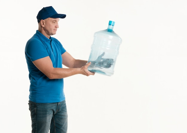 Side view of delivery man holding water bottle Free Photo