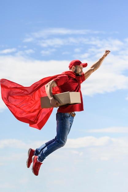 Вид сбоку доставщик в накидке супергероя Premium Фотографии