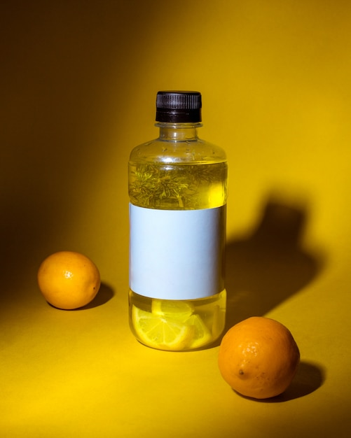 Side view of detox drink with lemon in a bottle on dark yellow Free Photo