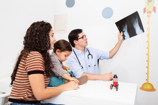 Medico di vista laterale che tiene una radiografia Foto Gratuite