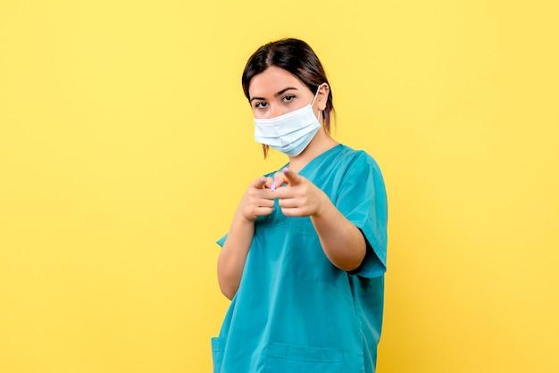 La vista laterale di un medico in maschera è orgogliosa di aver curato i pazienti con coronavirus Foto Gratuite