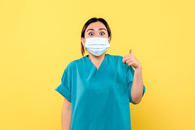 La vista laterale di un medico in maschera sta parlando dei sintomi del coronavirus Foto Gratuite