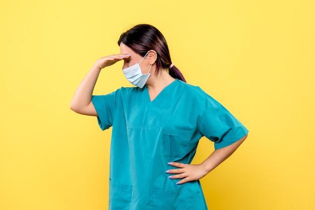 La vista laterale del dottore in una maschera sta pensando ai pazienti con covid Foto Gratuite