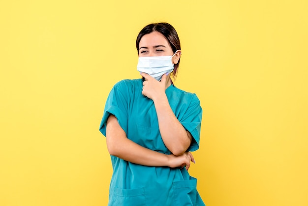 La vista laterale del dottore in una maschera sta pensando ai sintomi del covid Foto Gratuite