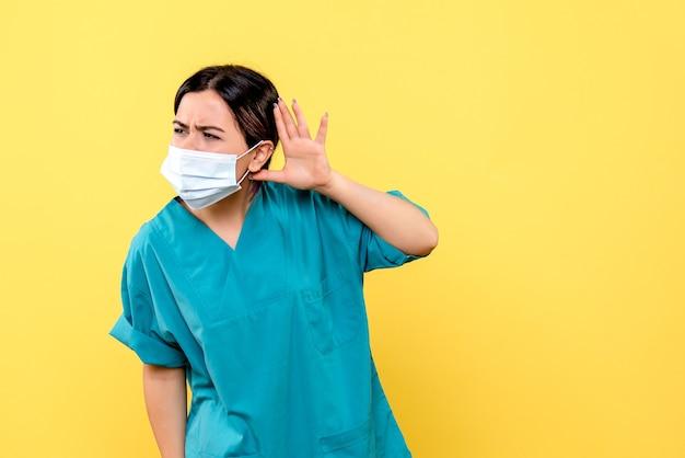 La vista laterale di un medico in maschera ascolta i reclami dei pazienti con covid Foto Gratuite