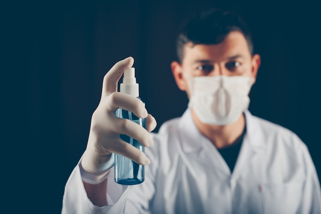 Side view doctor with mask holding medical spray in his hand Free Photo