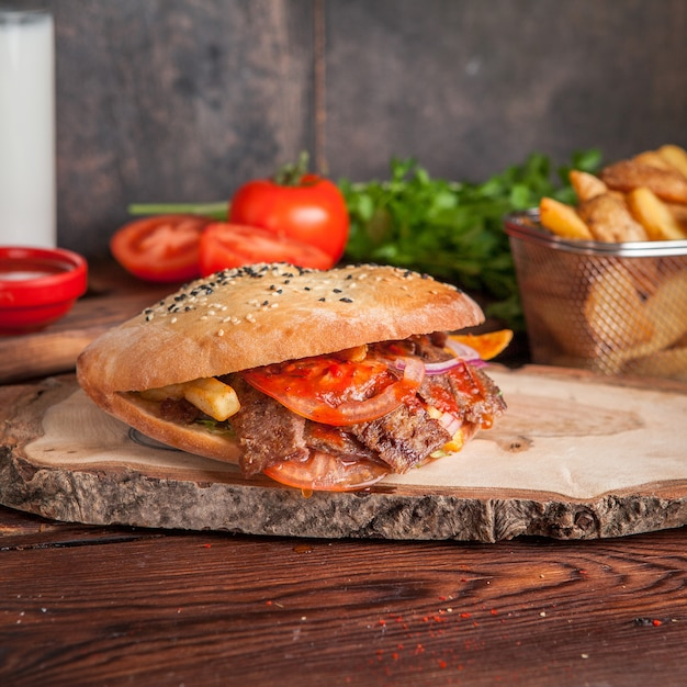 Вид сбоку донер с помидорами и жареным картофелем и зеленью в посуде Бесплатные Фотографии