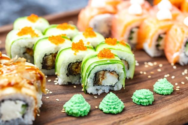 Rotolo del drago di vista laterale con i semi di sesamo e il wasabi del caviale di tobiko del pesce fritti cetriolo su un bordo Foto Gratuite