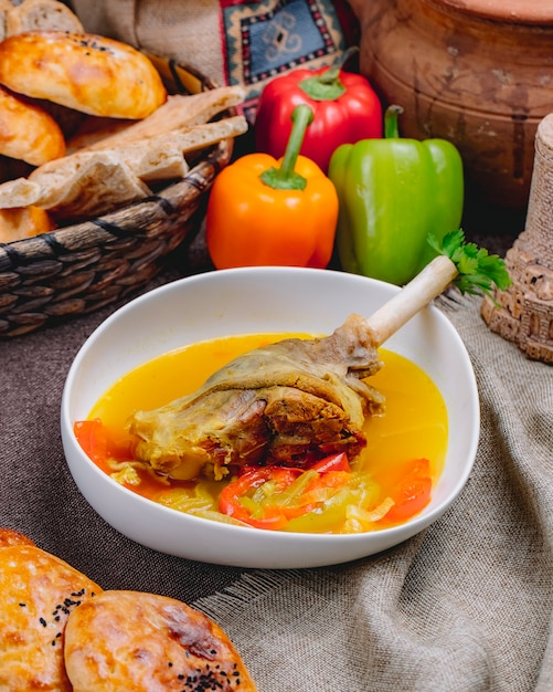 Side view of duck leg in bouillon with vegetables in a white bowl Free Photo