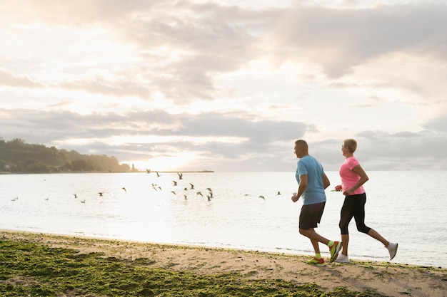 Side view of elder couple jogging on the beach Free Photo