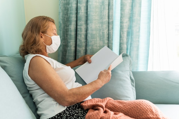 Side view of elder woman with medical mask at home during the pandemic reading a book Free Photo
