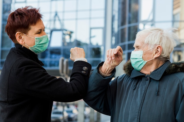 Side view of elder women using elbows to salute each other while wearing medical masks Free Photo