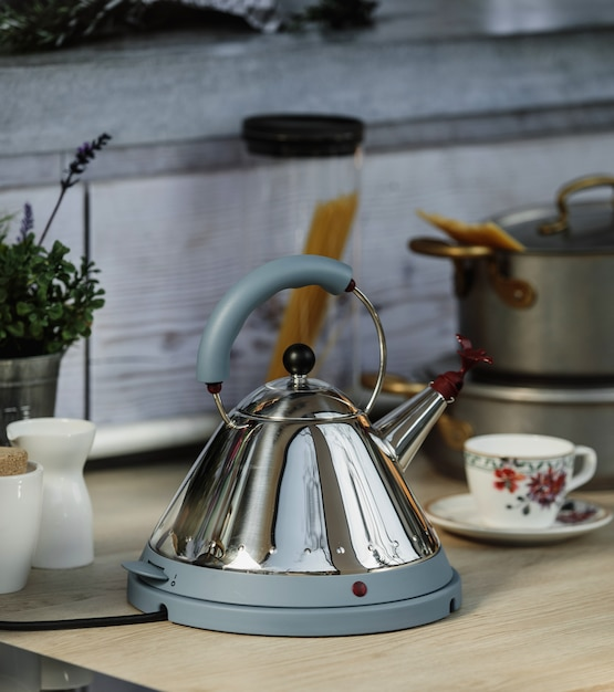 Side view of electric modern kettle with whistle on a wooden table in kitchen Free Photo
