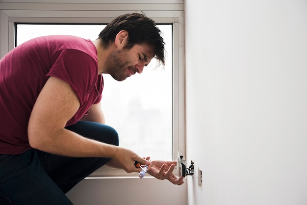 Side view of electrician fixing plug socket on white wall Free Photo