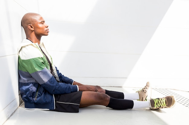 Side view of a exhausted young male athlete relaxing against white wall Free Photo