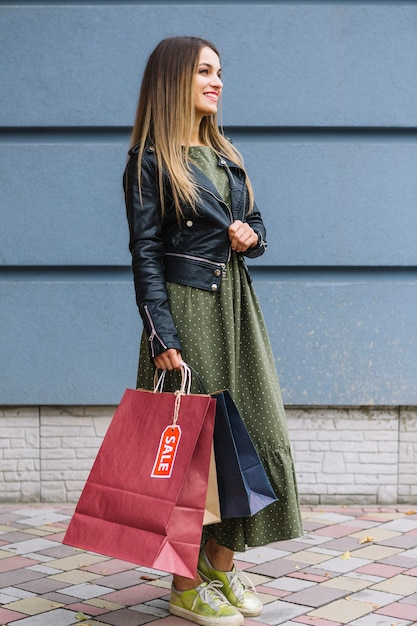 Side view of a fashionable young woman wearing jacket holding shopping bags in hand Free Photo