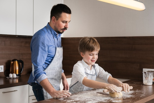 Side view father and son rolling dough Free Photo