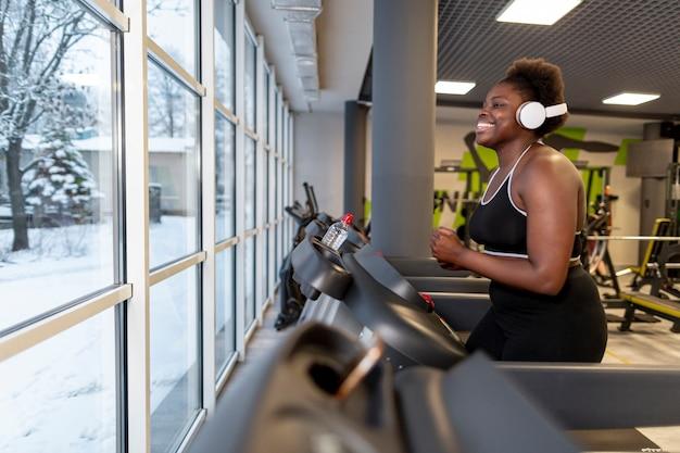 Вид сбоку девушки в тренажерном зале, бег на беговой дорожке Бесплатные Фотографии