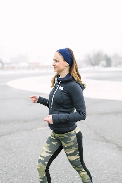 Side view of a female athlete exercising in winter Free Photo