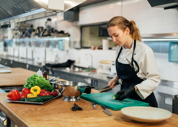 Vista laterale della donna chef in cucina per affettare le verdure Foto Gratuite