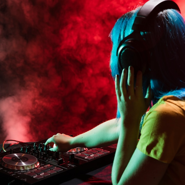 Side view female dj at control panel Free Photo