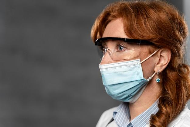 Vista laterale della dottoressa con maschera medica e copia spazio Foto Gratuite