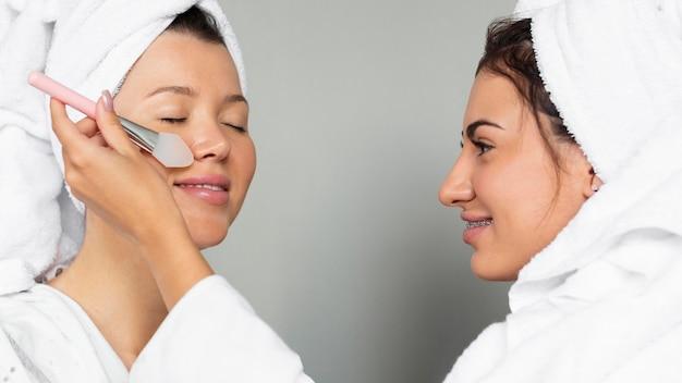 Vista laterale delle amiche che applicano prodotti per la cura della pelle Foto Gratuite
